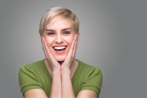 Smiling woman with beautiful teeth putting her hands on her face