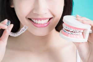 a woman holding clear braces and a mold of traditional braces