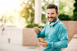 Smiling man with beautiful smile eating a healthy snack