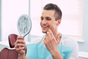 a young man smiling in the mirror at the dentist's office