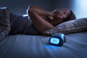 Person with sleep apnea in Spring Lake lies awake next to alarm clock