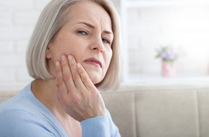 an older woman holding her jaw and wincing in pain
