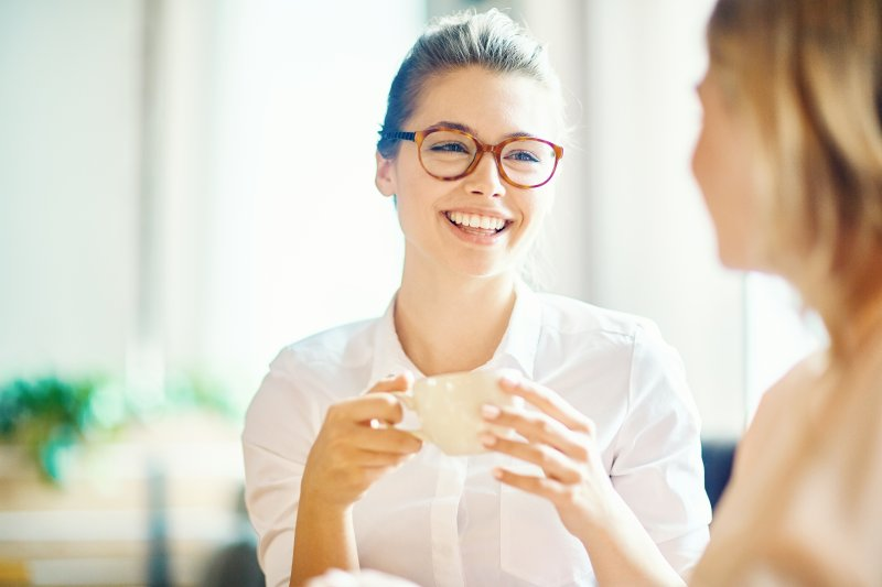 Closeup of woman smiling with friend while drinking tea