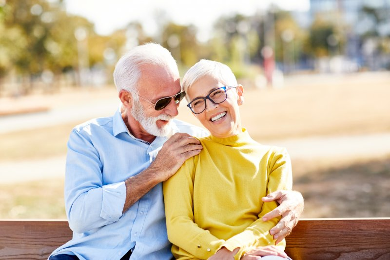 Senior couple smiling together on bench outside