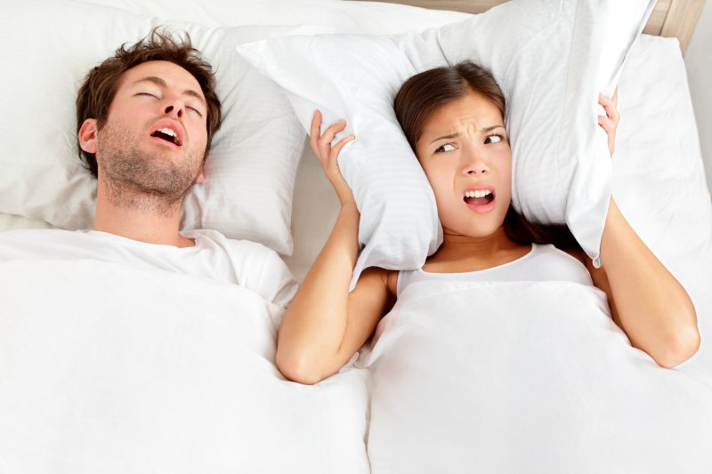 Woman covering ears with pillow next to snoring man
